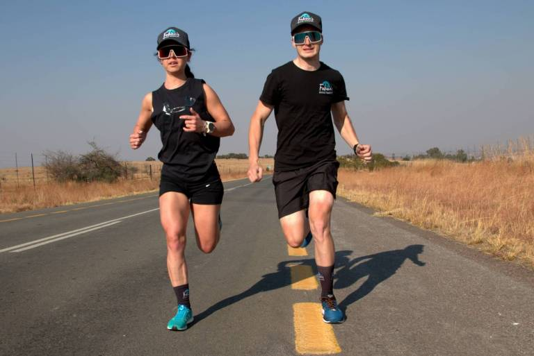 Lexi Claasen and Fabian Valsecchi running in the cradle of humankind training for ironman east london wearing black clothing with grey fabians bicycle transport cap