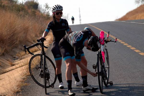 lexi claasen and fabian valsecchi fixing bicycles next to the road with pink bottles fabians bicycle transport cycling kit