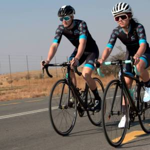 Fabian Valsecchi and Lexi Claasen cycling in the cradle of humankind wearing Fabians Bicycle Transport cycling kit on a chapter 2 rere and bianchi sempre black wearing a black and white suomy helmet and white specialized helmet