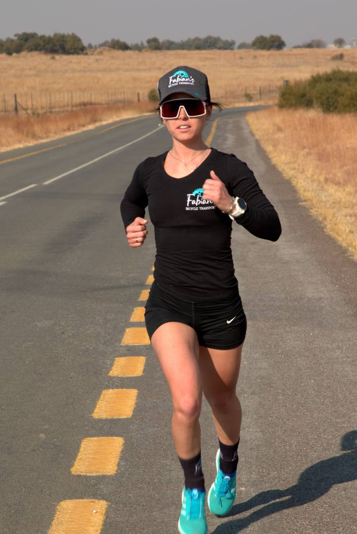 lexi claasen running on the road in the cradle of humankind wearing black with blue shoes