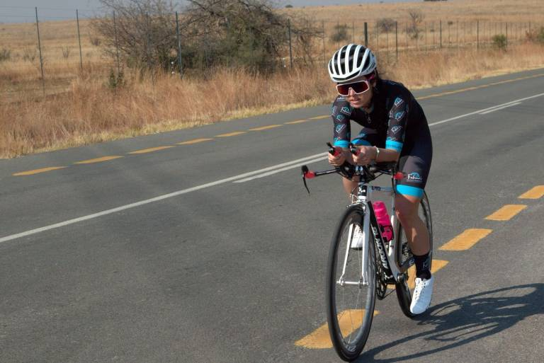 Lexi Claasen cycling on a white argon E112 triathlon bike wearing black and blue fabian's bicycle transport cycling kit pink water bottle white specialized helmet